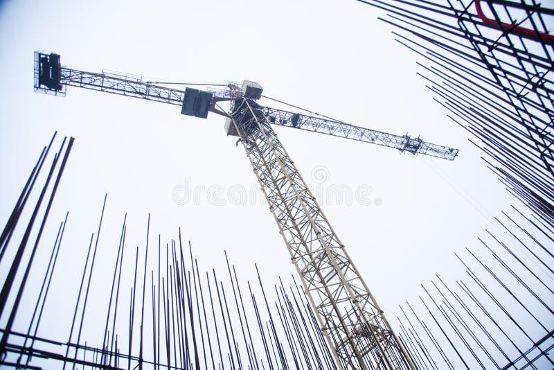 Betonowi filary na przemysłowej budowie Budynek drapacz chmur z żurawiem, narzędziami i wzmacniającymi stalowymi barami, obrazy royalty free