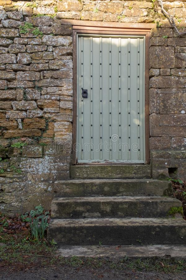 Betonowi progi prowadzi do nabijającego ćwiekami drzwi osadzającego w ścianie obraz royalty free