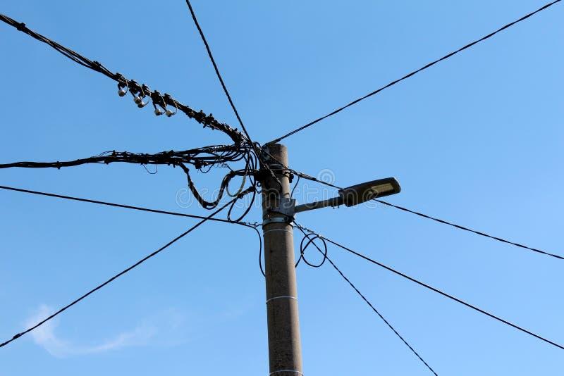Betonowy elektryczny oszczędnościowy słup z nowożytnym DOWODZONYM społeczeństwa światłem i wieloskładnikowymi elektrycznymi druta fotografia royalty free
