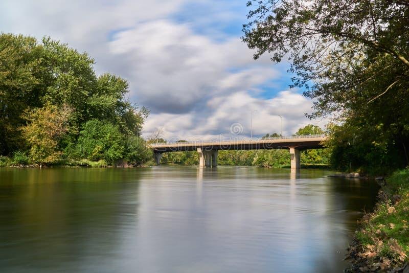 Betonowy most nad lis rzeką na chmurnym dniu fotografia stock