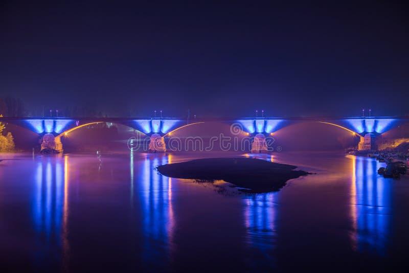 Betonowy most z pięknymi niebieskimi światłami odbitymi w jeziorze w nocy w Pavia, Włochy fotografia stock