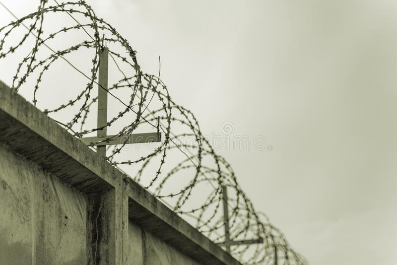 Betonowy ogrodzenie z drutem kolczastym przeciw szaremu niebu zdjęcie royalty free