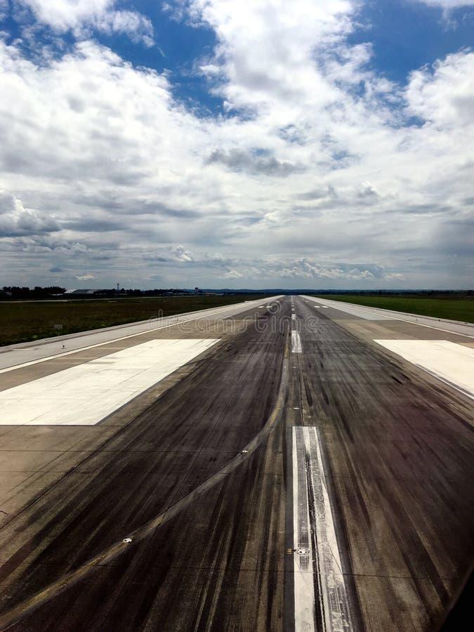 Betonowy pas startowy w pomniejszać perspektywę z czarnymi opon ocenami i białymi farb liniami w zielonym lotnisku zdjęcie royalty free