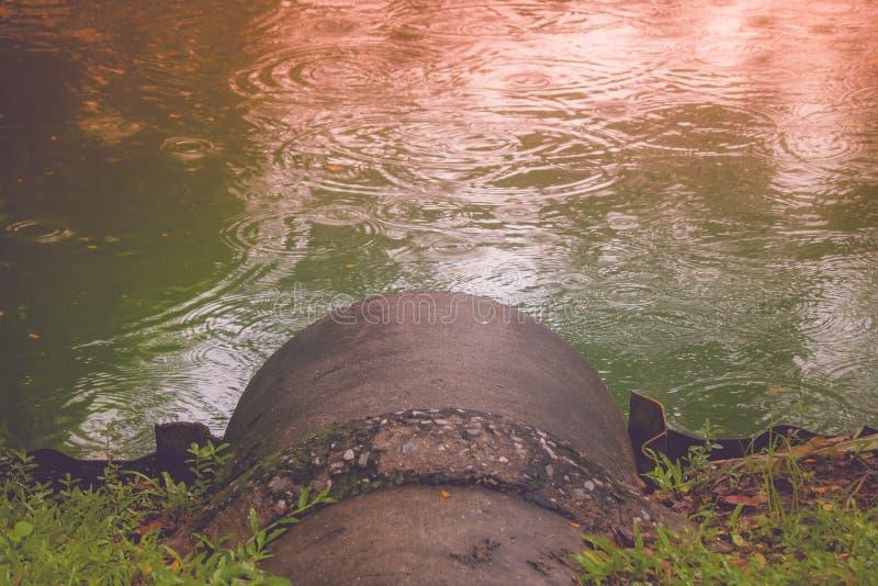 Betonröhre oder Rohrleitung für das Abwasser, das ausläuft, um mit Sonnenlicht matschig zu machen, denken über Wasseroberflächenh stockfotografie