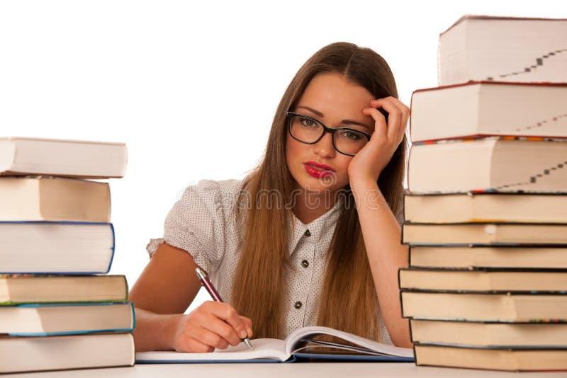 Betonte asiatische kaukasische Studentin, die in den Tonnen Büchern lernt stockfotografie