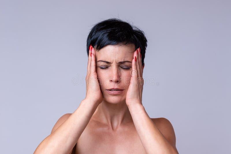 Betonte besorgte Frau mit Kopfschmerzen stockbild