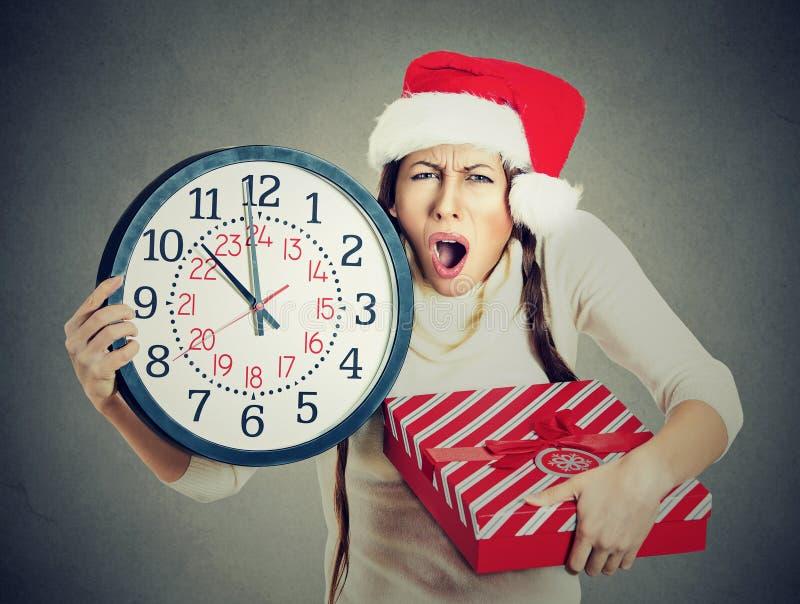 Betonte in Eile Frau, die Weihnachtsmann-Hut hält Uhrgeschenkbox trägt lizenzfreie stockbilder