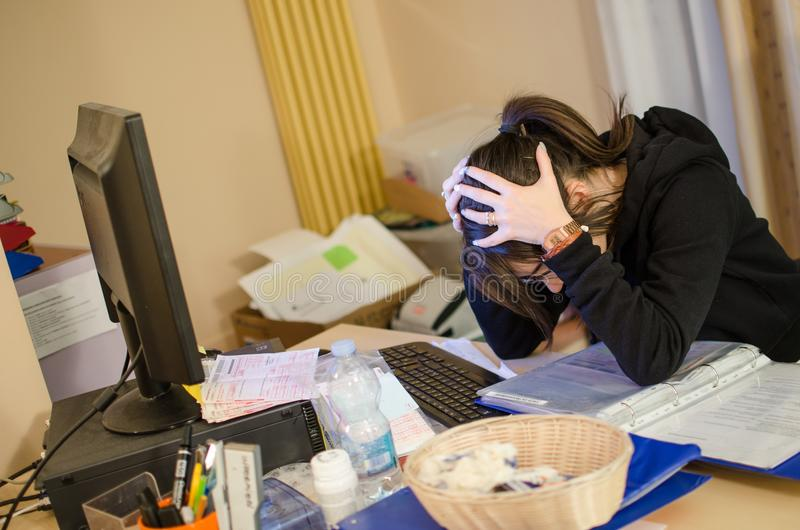Betonte Frau bei der Arbeit mit Computer vor ihr lizenzfreie stockbilder