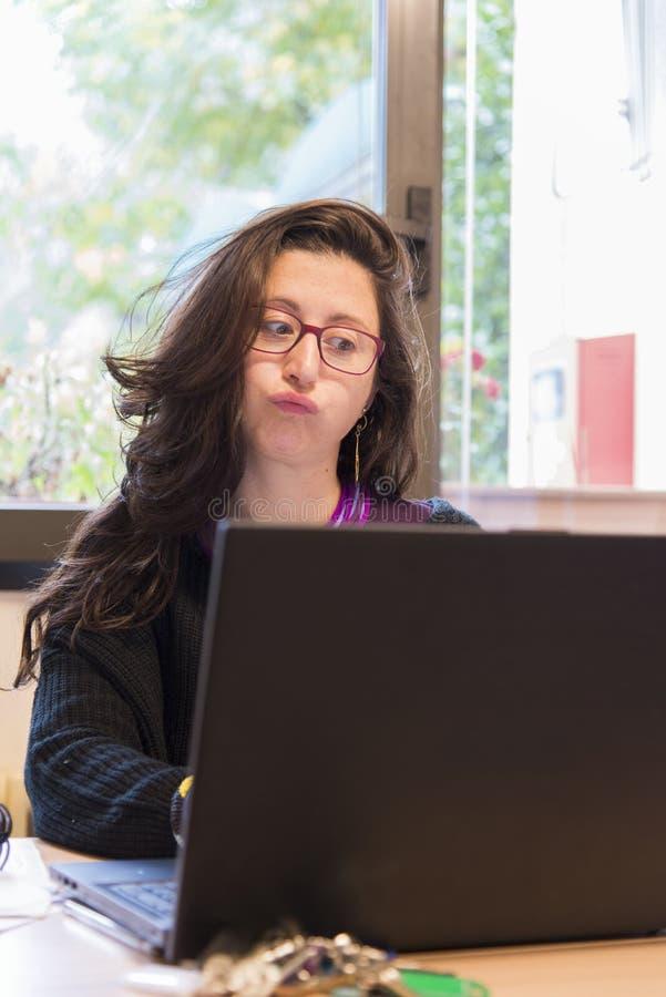 Betonte Frau bei der Arbeit mit Computer vor ihr stockfotografie