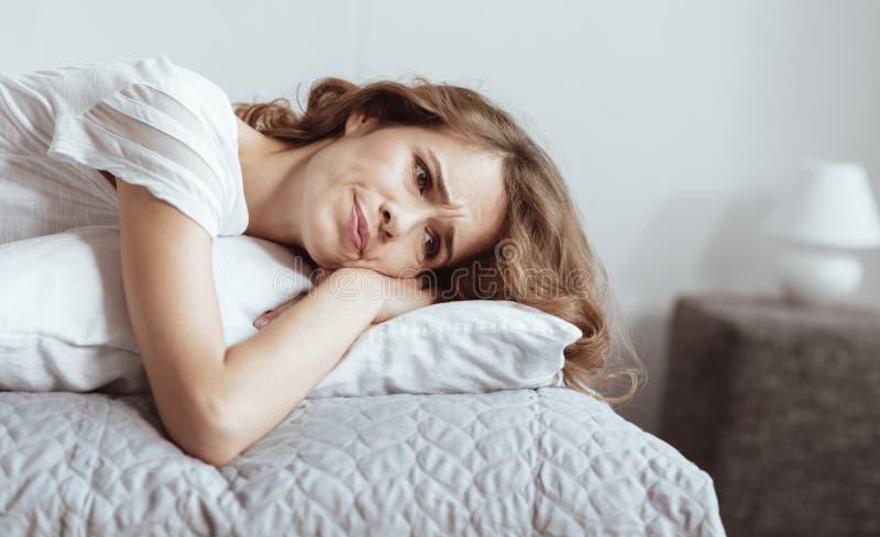 Betonte Frau, die auf Bett liegt und gesorgt erhält lizenzfreie stockfotos