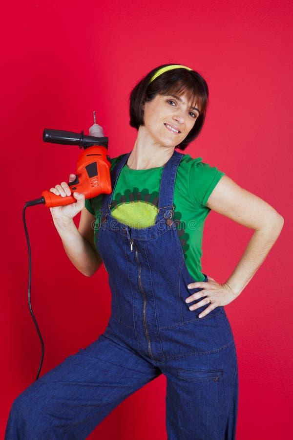 Betonte Frau, die ein elektrisches Bohrgerät anhält lizenzfreies stockbild