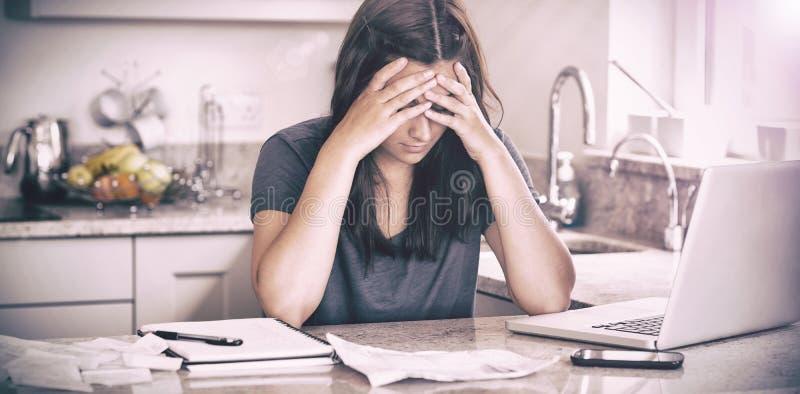 Betonte Frau, die unten Rechnungen betrachtet lizenzfreie stockfotografie