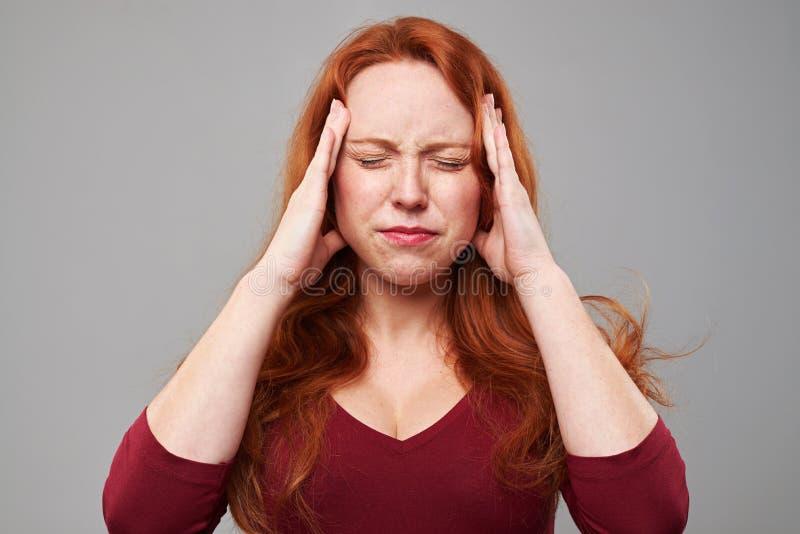 Betonte Frau mit den Kopfschmerzen, die ihre Hände auf Kopf halten stockfotografie