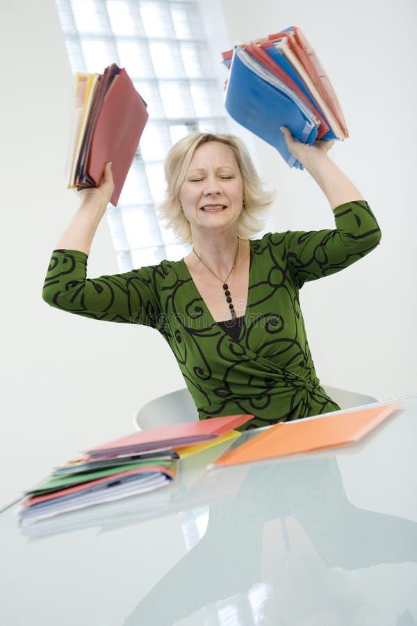Betonte Frau mit Faltblättern lizenzfreie stockbilder