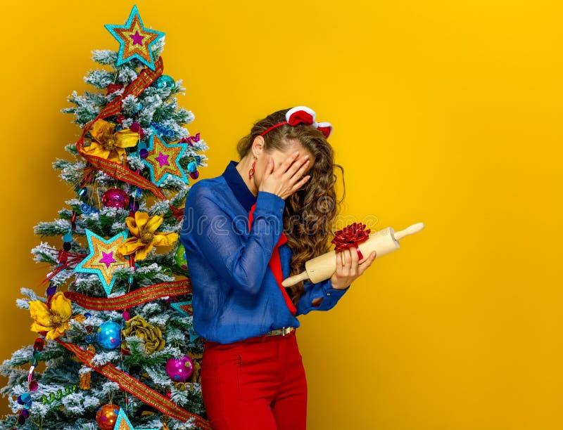 Betonte Frau unglücklich mit Weihnachtsgeschenk lizenzfreie stockbilder