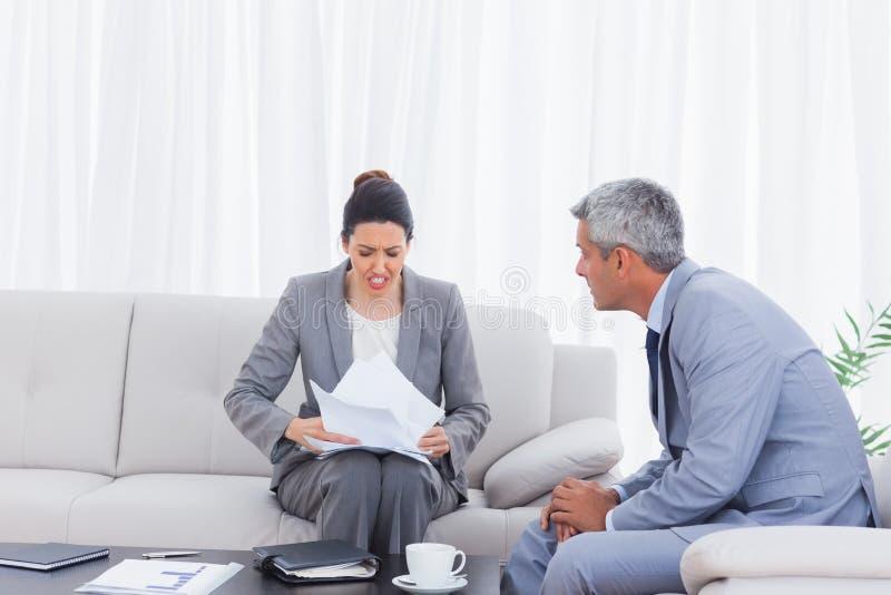 Betonte Geschäftsfrau, die Dokumente und das Geschäftsmannversuchen hält stockfoto