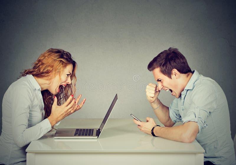 Betonte Geschäftsfrau mit dem Laptop, der bei Tisch mit dem verärgerten Mann schreit am Handy sitzt Negative Gefühle im Büroleben stockfotos