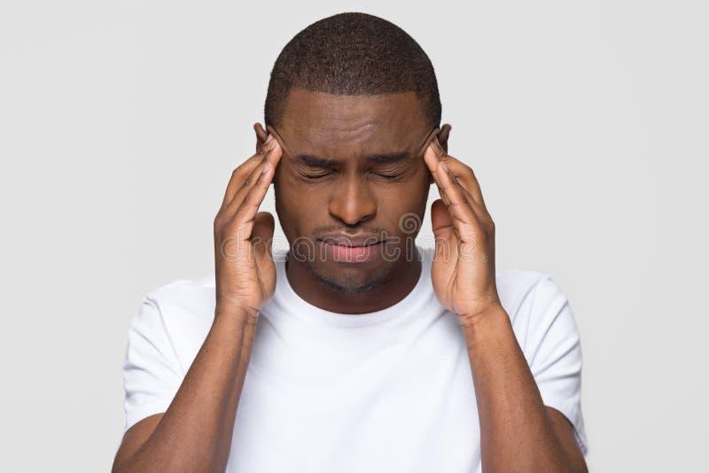 Betonte glaubende Schmerz des jungen Afroamerikanermannes, die schreckliche Kopfschmerzen haben lizenzfreie stockfotos