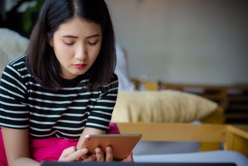 Betonte junge Berufsgeschäftsfrau unter Verwendung des Tablet-Computers in der Kaffeestube Asiatisches weibliches Sitzen auf Couc lizenzfreie stockfotografie