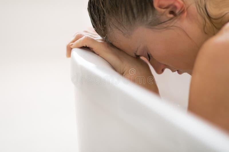 Betonte junge Frau, die in der Badewanne sitzt lizenzfreie stockfotos