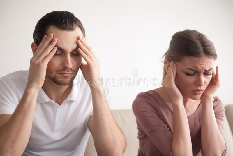 Betonte junge Paare, die unter Kopfschmerzen, rührender Kopf, F.E. leiden lizenzfreies stockbild