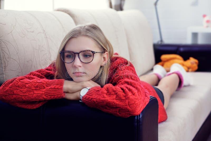 Betonte kaukasische Frau in den glases, die zu Hause auf Sofa liegen stockfotografie