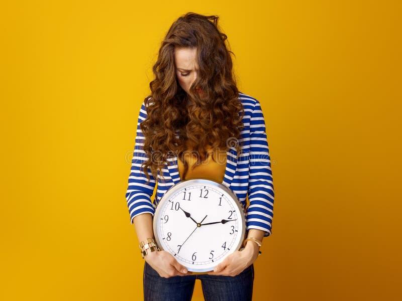 Betonte modische Frau gegen gelben Hintergrund mit Uhr lizenzfreies stockbild