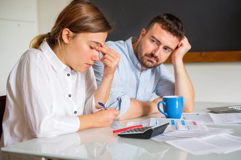 Betonte Paare, die zu Hause sitzen und unbezahlte Rechnungen überprüfen stockfotos
