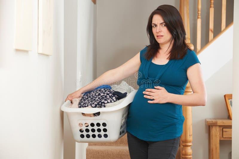 Betonte schwangere Frau, die zu Hause Aufgaben tut lizenzfreies stockbild