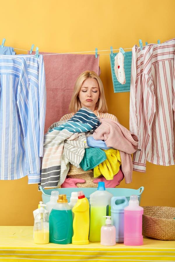 Betonte unglückliche Blondine, die zu Hause Wäscherei tun lizenzfreies stockbild