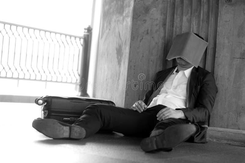 Betonter asiatischer Geschäftsmann bankrott mit dem Sitzen und des Buches nahen Gesicht am im Freien lizenzfreie stockfotografie