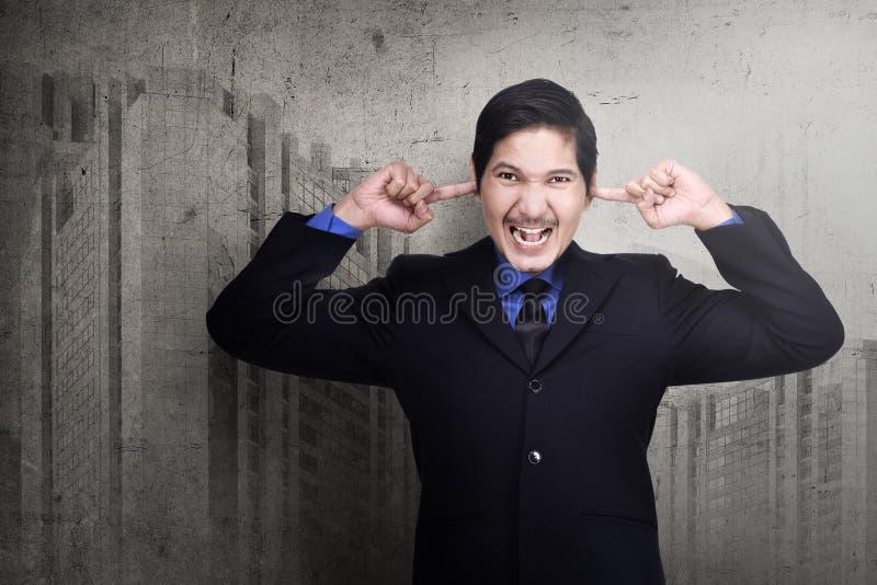 Betonter asiatischer Geschäftsmann, der seine Ohren mit den Fingern verstopft lizenzfreie stockbilder