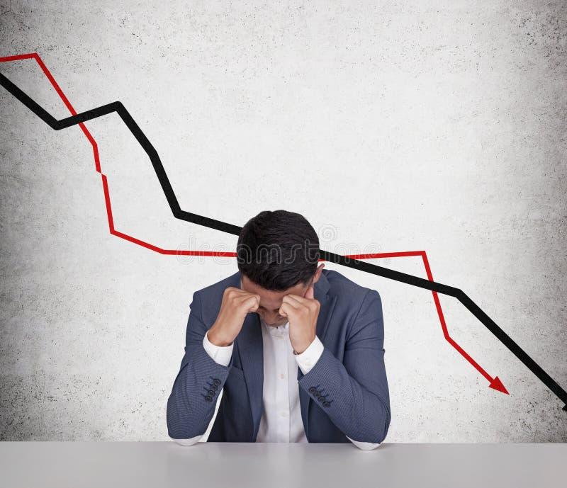 Betonter asiatischer Geschäftsmann und abfallende Diagramme stockfotos