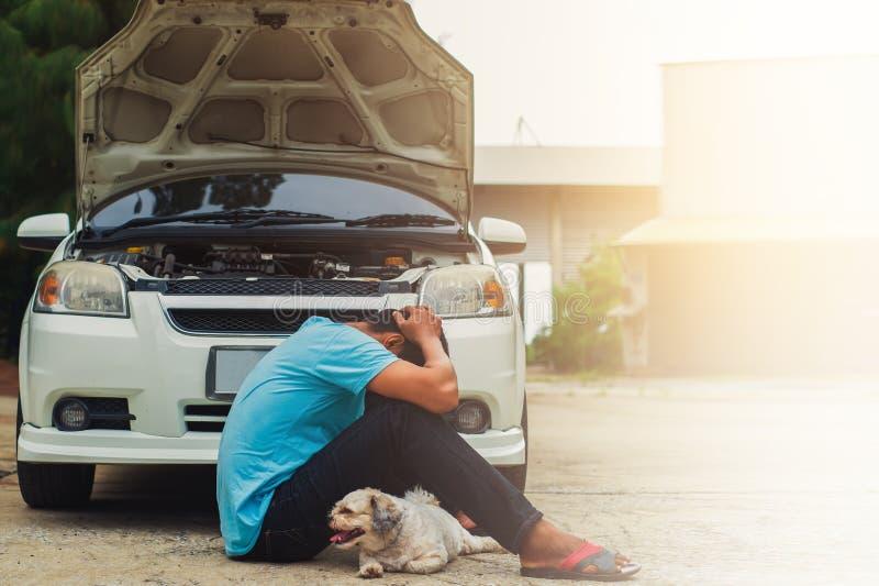 Betonter asiatischer Mann mit Hundesitzendem Kopf in den Händen wegen des bro lizenzfreie stockbilder