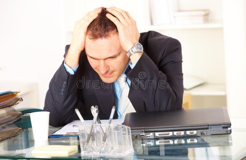 Betonter Geschäftsmann, der am Schreibtisch sitzt lizenzfreie stockfotografie