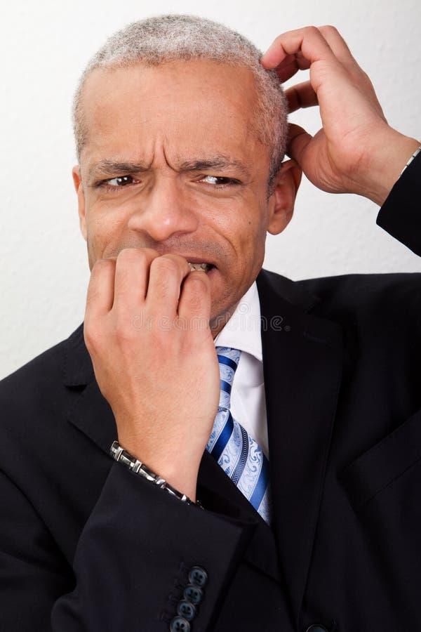 Betonter Geschäftsmann, der seine Nägel beißt stockfotografie