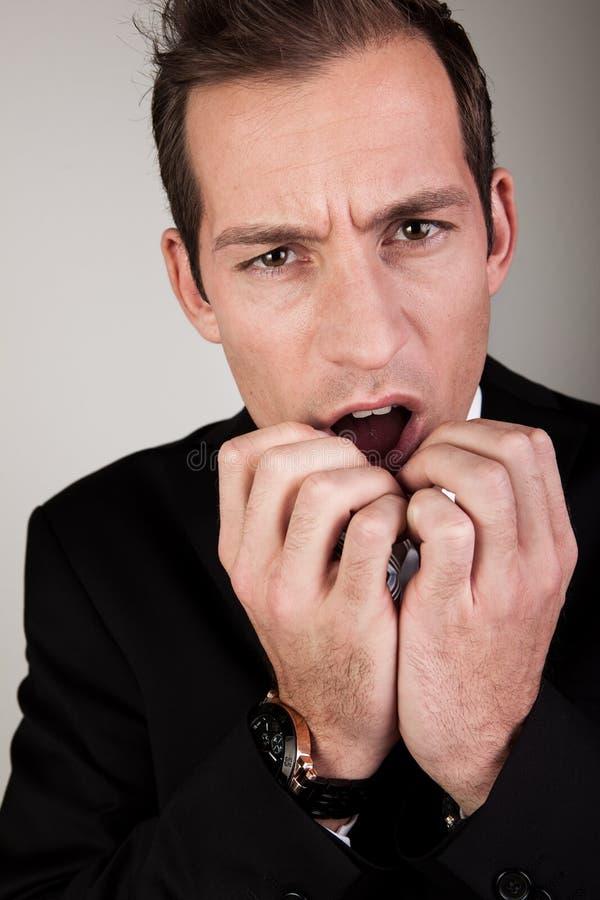 Betonter Geschäftsmann, der seine Nägel beißt lizenzfreie stockbilder