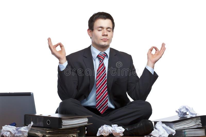 Betonter Geschäftsmann meditiert am Schreibtisch im Büro lizenzfreie stockbilder