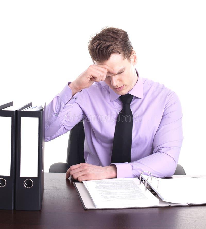 Betonter Geschäftsmann am Schreibtisch lizenzfreies stockfoto