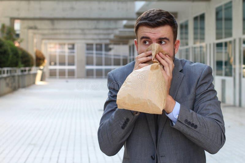 Betonter heraus Mann, der durch Papiertüte atmet lizenzfreie stockfotos