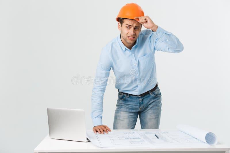 Betonter junger Erbauer, der die Kopfschmerzen oder Migräne schaut erschöpft und gesorgt auf weißem Hintergrund mit hat stockfotos