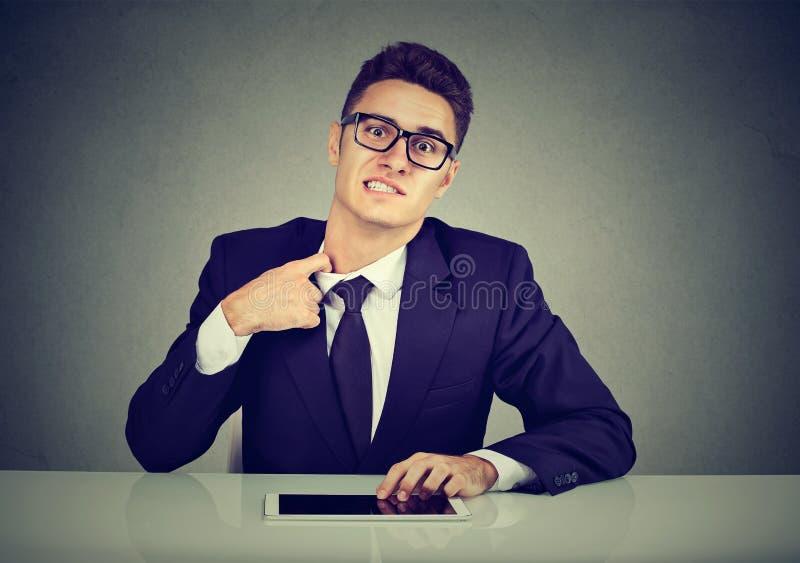 Betonter junger Geschäftsmann, der sein Hemd auf seinem Hals unbequem mit zu fester Bindung und formeller Kleidung zieht lizenzfreie stockbilder
