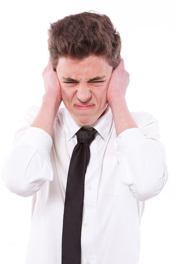 Betonter Kerl, der seine Ohren, zu viele Geräusche bedeckt lizenzfreie stockfotos