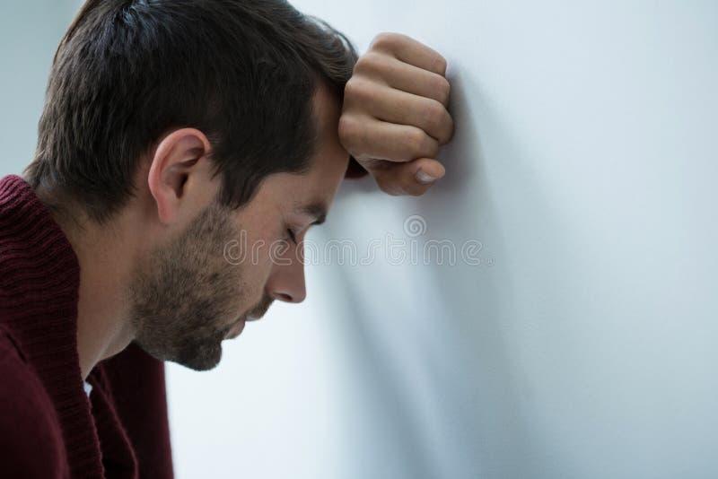 Betonter Mann, der auf Wand sich lehnt stockfotografie