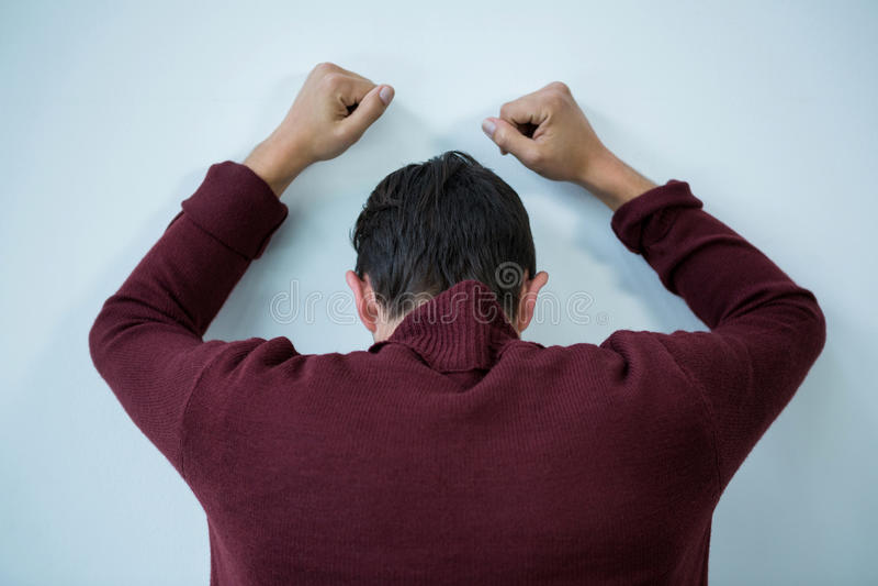 Betonter Mann, der auf Wand sich lehnt lizenzfreie stockfotografie