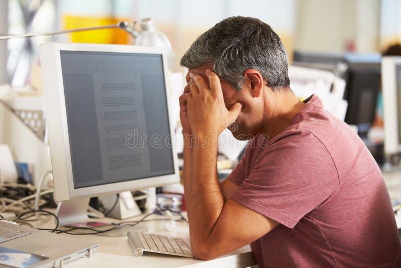 Betonter Mann, der am Schreibtisch im beschäftigten kreativen Büro arbeitet lizenzfreie stockfotos