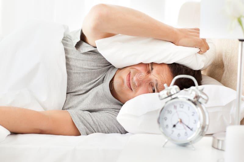 Betonter Mann, der sein Alarmuhrklingeln betrachtet lizenzfreies stockbild