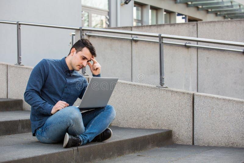 Betonter Student, der für eine Prüfung sich vorbereitet stockfotografie