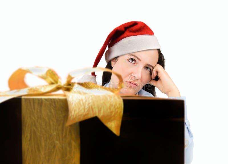 Betontes Fraueneinkaufen für die Geschenke, welche die Weihnachtsgeschenke tragen roten Sankt-Hut schaut verärgert und beunruhigt stockbilder