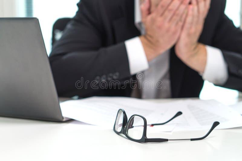 Betontes Geschäftsmann-Bedeckungsgesicht mit den Händen im Büro lizenzfreie stockfotos